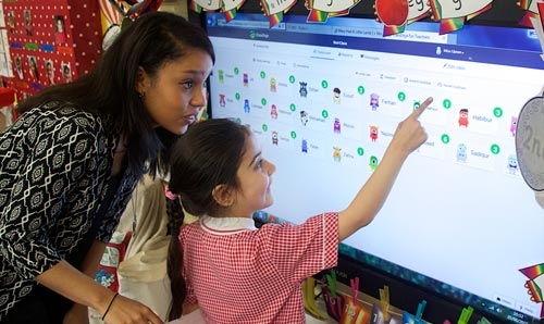 Pupil and teacher using touch screen display in classroom