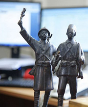 Metallic figurines in front of computer monitor